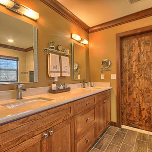 Réalisation d'une salle de bain principale tradition de taille moyenne avec un lavabo encastré, un placard à porte shaker, des portes de placard en bois brun, un plan de toilette en quartz modifié, une baignoire posée, un combiné douche/baignoire, un WC séparé, un carrelage beige, des carreaux de porcelaine, un mur jaune et un sol en carrelage de porcelaine.