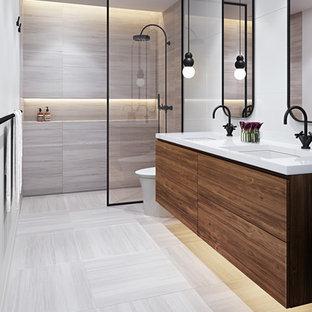 マイアミの小さいトランジショナルスタイルのおしゃれな浴室 (フラットパネル扉のキャビネット、中間色木目調キャビネット、バリアフリー、一体型トイレ、グレーのタイル、大理石タイル、白い壁、大理石の床、アンダーカウンター洗面器、クオーツストーンの洗面台、フローティング洗面台、グレーの床) の写真