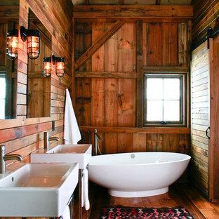 Modelo de cuarto de baño rústico con bañera exenta y lavabo tipo consola