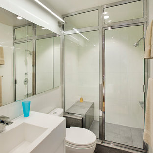 Small trendy 3/4 white tile and porcelain tile concrete floor and gray floor alcove shower photo in New York with flat-panel cabinets, white cabinets, a one-piece toilet, white walls, a console sink and a hinged shower door
