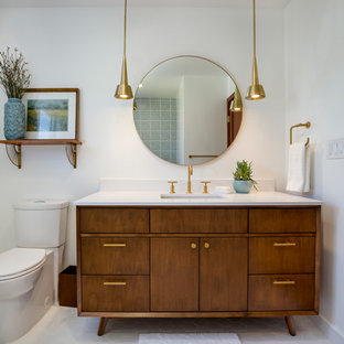 Inspiration for a mid-sized 1960s white tile and ceramic tile white floor and porcelain tile bathroom remodel in Los Angeles with medium tone wood cabinets, white walls, quartz countertops, furniture-like cabinets, a two-piece toilet, an undermount sink and a hinged shower door