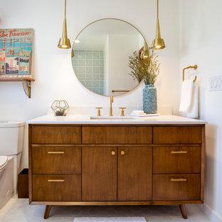 ロサンゼルスの中サイズのミッドセンチュリースタイルのおしゃれな浴室 (中間色木目調キャビネット、シャワー付き浴槽、白いタイル、セラミックタイル、白い壁、クオーツストーンの洗面台、家具調キャビネット、ドロップイン型浴槽、分離型トイレ、磁器タイルの床、アンダーカウンター洗面器、白い床、開き戸のシャワー) の写真