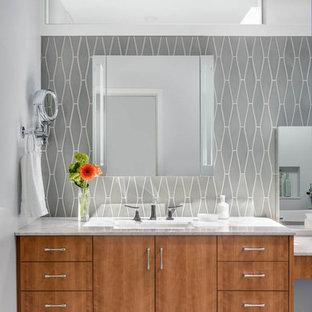 Idee per una grande stanza da bagno moderna con ante lisce, ante in legno scuro, vasca freestanding, doccia ad angolo, piastrelle grigie, piastrelle di vetro, pareti grigie, pavimento con piastrelle in ceramica, lavabo sottopiano, top in marmo, pavimento grigio e porta doccia a battente