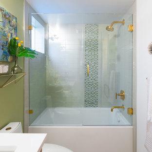 シアトルの中サイズのミッドセンチュリースタイルのおしゃれなマスターバスルーム (フラットパネル扉のキャビネット、淡色木目調キャビネット、ドロップイン型浴槽、コーナー設置型シャワー、ビデ、青いタイル、ガラスタイル、白い壁、淡色無垢フローリング、壁付け型シンク、珪岩の洗面台、白い床、開き戸のシャワー) の写真