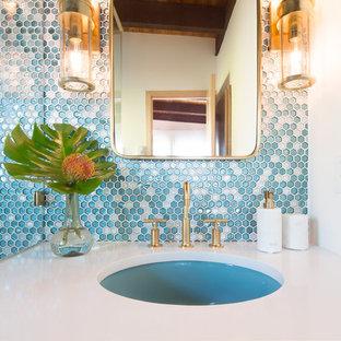 Foto di una stanza da bagno padronale minimalista di medie dimensioni con ante lisce, ante in legno chiaro, doccia ad angolo, bidè, piastrelle blu, piastrelle di vetro, pareti bianche, parquet chiaro, lavabo sospeso, top in quarzite, pavimento bianco e porta doccia a battente