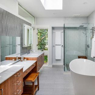 Неиссякаемый источник вдохновения для домашнего уюта: главная ванная комната в стиле ретро с плоскими фасадами, фасадами цвета дерева среднего тона, отдельно стоящей ванной, угловым душем, серой плиткой, серыми стенами, врезной раковиной, серым полом, душем с распашными дверями и серой столешницей