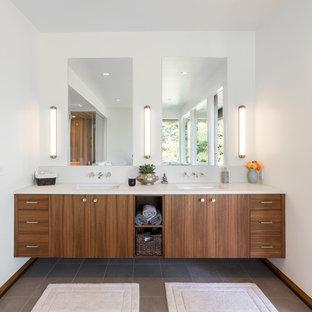 Exemple d'une très grand salle de bain principale rétro avec un placard à porte plane, une baignoire indépendante, une douche double, un mur blanc, un sol en carrelage de porcelaine, un lavabo encastré, un plan de toilette en quartz modifié, un sol gris, une cabine de douche à porte battante et des portes de placard en bois brun.