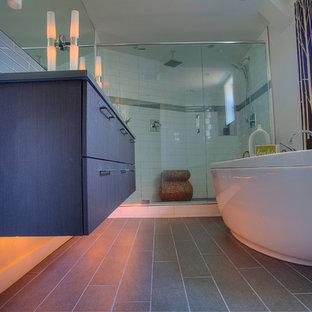 Idéer för att renovera ett mellanstort funkis en-suite badrum, med släta luckor, skåp i mörkt trä, bänkskiva i kvarts, vit kakel, keramikplattor, ett fristående badkar, en dubbeldusch, en toalettstol med separat cisternkåpa, ett integrerad handfat, grå väggar och klinkergolv i porslin