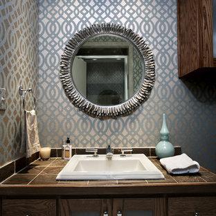Foto de cuarto de baño con ducha, retro, con encimera de azulejos, paredes multicolor, lavabo encastrado, armarios tipo vitrina, baldosas y/o azulejos grises y puertas de armario de madera en tonos medios