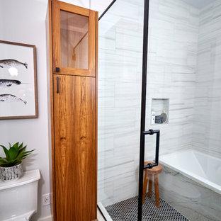 Aménagement d'une salle de bain principale rétro de taille moyenne avec un placard à porte plane, des portes de placard en bois brun, une baignoire en alcôve, un espace douche bain, un WC à poser, un carrelage noir et blanc, des carreaux de porcelaine, un mur blanc, un sol en carreaux de ciment, une vasque, un plan de toilette en quartz, un sol noir, une cabine de douche à porte battante, un plan de toilette blanc, une niche, meuble double vasque, meuble-lavabo suspendu et du lambris de bois.