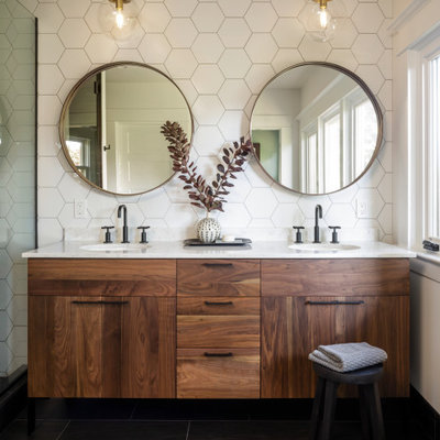 Bathroom - mid-sized mid-century modern master white tile and ceramic tile porcelain tile, black floor and double-sink bathroom idea in Portland with medium tone wood cabinets, white walls, an undermount sink, quartz countertops, a hinged shower door, white countertops, a niche and a freestanding vanity
