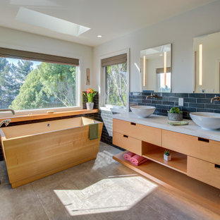 Example of a 1950s double-sink bathroom design in San Francisco with an undermount tub, laminate countertops, flat-panel cabinets, medium tone wood cabinets and a floating vanity