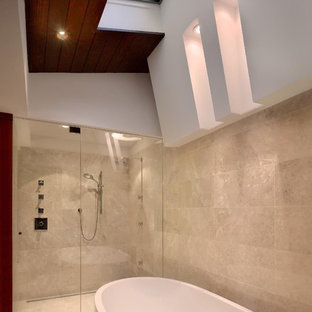 Example of a mid-sized trendy master beige tile and travertine tile light wood floor and brown floor bathroom design in Atlanta with flat-panel cabinets, dark wood cabinets, beige walls, an integrated sink, stainless steel countertops and a hinged shower door