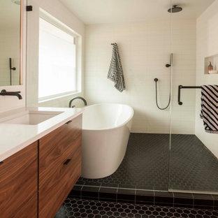 Idéer för mellanstora retro vitt en-suite badrum, med öppna hyllor, ett fristående badkar, våtrum, en toalettstol med hel cisternkåpa, vit kakel, keramikplattor, vita väggar, klinkergolv i porslin, ett integrerad handfat, bänkskiva i kvartsit, svart golv och dusch med gångjärnsdörr
