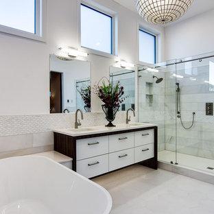 Cette image montre une très grand douche en alcôve principale design avec un placard à porte plane, des portes de placard blanches, une baignoire indépendante, un carrelage blanc, des carreaux de porcelaine, un mur blanc, un sol en carrelage de céramique, un plan de toilette en quartz modifié, un sol blanc, une cabine de douche à porte coulissante, un plan de toilette blanc, un lavabo encastré et meuble double vasque.