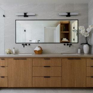 Ejemplo de cuarto de baño principal, retro, con armarios con paneles lisos, puertas de armario de madera clara, bañera exenta, baldosas y/o azulejos grises, paredes grises, lavabo bajoencimera, suelo gris y encimeras marrones