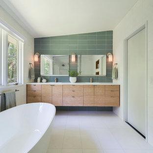 Imagen de cuarto de baño retro, grande, con bañera exenta, lavabo bajoencimera, armarios con paneles lisos, puertas de armario de madera clara, encimera de mármol, baldosas y/o azulejos verdes, baldosas y/o azulejos de vidrio, paredes blancas y encimeras blancas