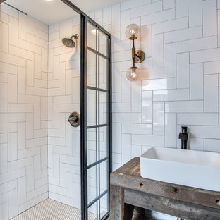 Modelo de cuarto de baño con ducha, rural, pequeño, con armarios abiertos, puertas de armario de madera oscura, ducha esquinera, baldosas y/o azulejos blancos, baldosas y/o azulejos de cerámica, paredes grises, lavabo sobreencimera, encimera de madera y ducha con puerta corredera