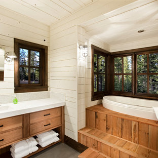 Mountain style 3/4 gray floor and concrete floor drop-in bathtub photo with flat-panel cabinets, medium tone wood cabinets, white walls and an undermount sink