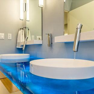 Foto de cuarto de baño principal, retro, de tamaño medio, con armarios con paneles lisos, puertas de armario de madera clara, paredes grises, lavabo sobreencimera y encimera de vidrio