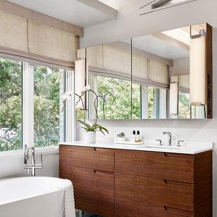 Immagine di una stanza da bagno padronale design di medie dimensioni con consolle stile comò, vasca freestanding, pareti bianche, pavimento con piastrelle in ceramica, lavabo sottopiano, top in superficie solida, ante in legno scuro e top bianco