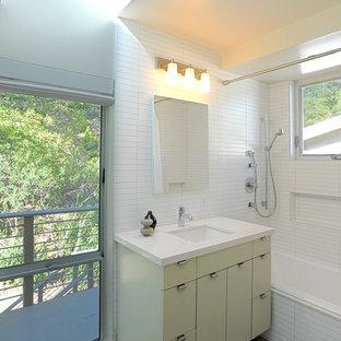 Ispirazione per una stanza da bagno minimal con lavabo sottopiano, ante lisce, ante verdi, vasca ad alcova, vasca/doccia e piastrelle bianche
