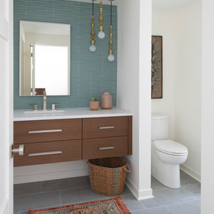 Inspiration for a large mid-century modern 3/4 blue tile gray floor bathroom remodel in Minneapolis with an undermount sink, flat-panel cabinets, dark wood cabinets, white walls and white countertops