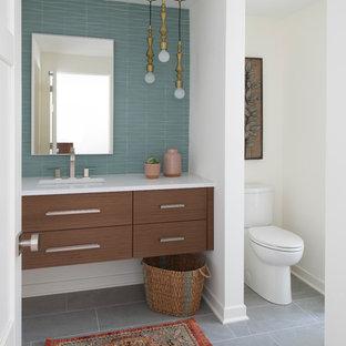 Foto de cuarto de baño con ducha, retro, grande, con lavabo bajoencimera, armarios con paneles lisos, puertas de armario de madera en tonos medios, baldosas y/o azulejos azules, paredes blancas, suelo gris y encimeras blancas
