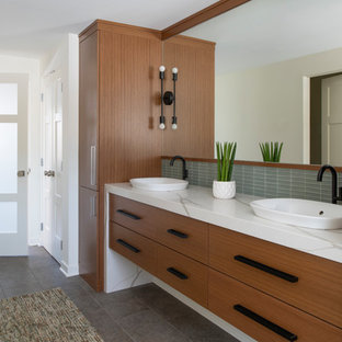 60 tals inredning av ett stort vit vitt en-suite badrum, med släta luckor, skåp i mellenmörkt trä, grå kakel, vita väggar, ett fristående handfat och grått golv
