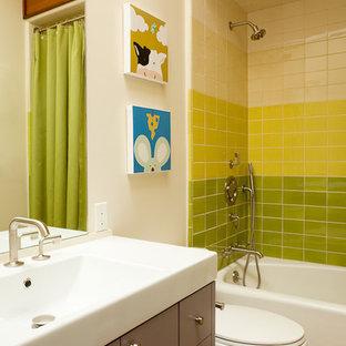 Modelo de cuarto de baño infantil, moderno, grande, con armarios con paneles lisos, paredes blancas, suelo de corcho, encimera de acrílico, bañera empotrada, combinación de ducha y bañera, sanitario de una pieza, baldosas y/o azulejos verdes, baldosas y/o azulejos de cemento y lavabo tipo consola