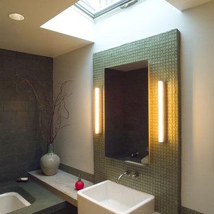 Esempio di una stanza da bagno minimalista con lavabo sospeso, top in saponaria, vasca sottopiano, piastrelle verdi, piastrelle di vetro, pareti verdi e pavimento in linoleum