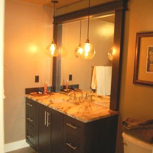 ポートランドの小さいコンテンポラリースタイルのおしゃれな子供用バスルーム (磁器タイルの床、アンダーカウンター洗面器、シェーカースタイル扉のキャビネット、濃色木目調キャビネット、大理石の洗面台、置き型浴槽、シャワー付き浴槽、分離型トイレ、グレーのタイル、磁器タイル、茶色い壁) の写真