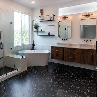 На фото: ванная комната в стиле ретро с плоскими фасадами, коричневыми фасадами, отдельно стоящей ванной, угловым душем, черно-белой плиткой, керамогранитной плиткой, белыми стенами, полом из керамогранита, настольной раковиной, столешницей из искусственного кварца, черным полом, душем с распашными дверями, белой столешницей, сиденьем для душа, тумбой под две раковины и подвесной тумбой с