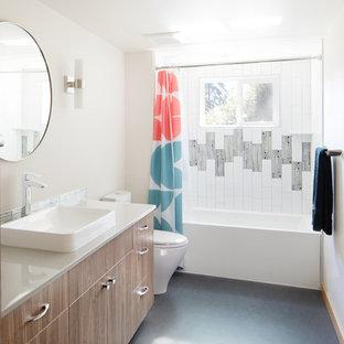 Свежая идея для дизайна: ванная комната среднего размера в стиле ретро с плоскими фасадами, темными деревянными фасадами, ванной в нише, душем над ванной, унитазом-моноблоком, белой плиткой, белыми стенами, полом из линолеума, накладной раковиной, синим полом и шторкой для ванной - отличное фото интерьера
