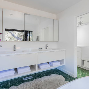 Inspiration for a 1960s master cement tile floor and green floor bathroom remodel in San Francisco with flat-panel cabinets, white cabinets, engineered quartz countertops, white countertops, white walls and an integrated sink