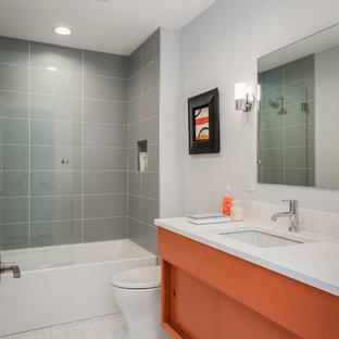 Ispirazione per una stanza da bagno per bambini minimalista di medie dimensioni con ante lisce, ante arancioni, vasca ad alcova, vasca/doccia, piastrelle grigie, piastrelle in ceramica, pareti grigie, pavimento con piastrelle in ceramica, lavabo sottopiano, top in quarzo composito, pavimento bianco e top bianco
