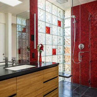 Example of a 1960s red tile and mosaic tile black floor walk-in shower design in San Francisco with flat-panel cabinets, medium tone wood cabinets, white walls, an undermount sink and black countertops