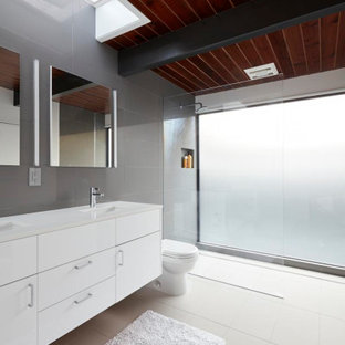 Bathroom - large 1950s master gray tile and porcelain tile porcelain floor, beige floor, double-sink and wood ceiling bathroom idea in San Francisco with flat-panel cabinets, white cabinets, a two-piece toilet, an undermount sink, white countertops, a niche and a floating vanity