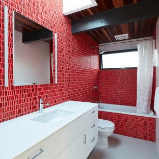 Aménagement d'une grand salle d'eau rétro avec un placard à porte plane, des portes de placard blanches, une baignoire posée, un combiné douche/baignoire, un carrelage rouge, un lavabo encastré, un sol gris, une cabine de douche avec un rideau, un plan de toilette blanc, meuble simple vasque, meuble-lavabo suspendu et un plafond en bois.