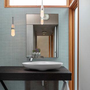 Ispirazione per una stanza da bagno moderna con piastrelle blu, piastrelle di vetro, pavimento in ardesia, lavabo a bacinella, top in legno, pavimento nero e top nero