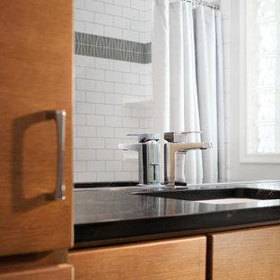 オマハの中くらいのミッドセンチュリースタイルのおしゃれな浴室 (フラットパネル扉のキャビネット、中間色木目調キャビネット、ドロップイン型浴槽、シャワー付き浴槽、分離型トイレ、白いタイル、サブウェイタイル、白い壁、アンダーカウンター洗面器、珪岩の洗面台、ベージュの床、シャワーカーテン) の写真