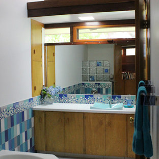 Mid-sized minimalist kids' blue tile and glass tile ceramic floor freestanding bathtub photo in San Francisco with flat-panel cabinets, medium tone wood cabinets, solid surface countertops and blue walls