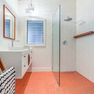 Foto de cuarto de baño con ducha, retro, de tamaño medio, con armarios con paneles lisos, puertas de armario blancas, ducha esquinera, baldosas y/o azulejos blancos, baldosas y/o azulejos de cerámica, paredes blancas, lavabo sobreencimera, encimera de cuarzo compacto, ducha abierta, encimeras blancas, suelo de ladrillo y suelo rojo