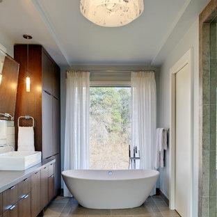 Неиссякаемый источник вдохновения для домашнего уюта: главная ванная комната в современном стиле с настольной раковиной, плоскими фасадами, темными деревянными фасадами, столешницей из известняка, отдельно стоящей ванной, инсталляцией, керамической плиткой, белыми стенами и полом из сланца