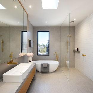 Modernes Badezimmer En Suite mit flächenbündigen Schrankfronten, hellbraunen Holzschränken, freistehender Badewanne, Nasszelle, grauen Fliesen, weißen Fliesen, grauer Wandfarbe, Aufsatzwaschbecken, Beton-Waschbecken/Waschtisch, grauem Boden und offener Dusche in Melbourne