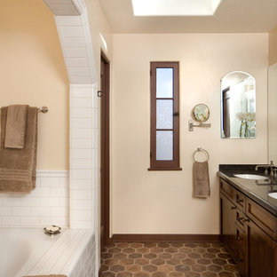 Inspiration for a mid-sized mediterranean master bathroom in Los Angeles with brown tile, beige walls, terra-cotta floors, shaker cabinets, dark wood cabinets, an undermount sink, an alcove tub, a corner shower and brown floor.