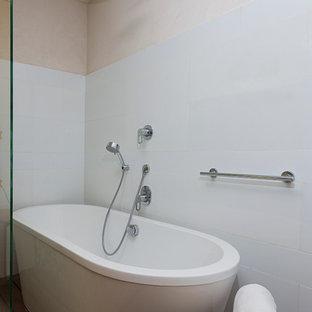 Diseño de cuarto de baño principal, moderno, pequeño, con lavabo sobreencimera, armarios tipo vitrina, encimera de madera, bañera exenta, baldosas y/o azulejos marrones y suelo de contrachapado