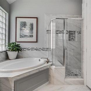 Ejemplo de cuarto de baño principal, clásico renovado, de tamaño medio, con puertas de armario grises, ducha esquinera, azulejos en listel, paredes grises, lavabo bajoencimera, ducha con puerta con bisagras, armarios con paneles con relieve, bañera esquinera, baldosas y/o azulejos blancas y negros, baldosas y/o azulejos grises, baldosas y/o azulejos multicolor, baldosas y/o azulejos blancos, suelo de mármol, suelo blanco y encimeras blancas