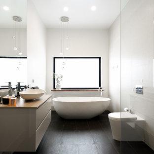 Bild på ett funkis beige beige en-suite badrum, med släta luckor, beige skåp, ett fristående badkar, en öppen dusch, en toalettstol med hel cisternkåpa, vit kakel, ett fristående handfat, träbänkskiva, svart golv och med dusch som är öppen