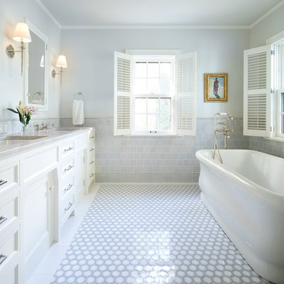 Freestanding bathtub - traditional gray tile gray floor freestanding bathtub idea in Minneapolis with recessed-panel cabinets, white cabinets, gray walls, an undermount sink and gray countertops
